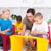 preschool students and female teacher in kindergarten