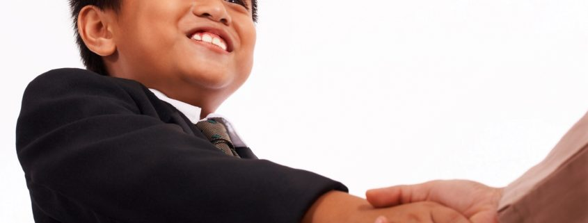 Boy In A Formal Suit Shaking Hands With Someone