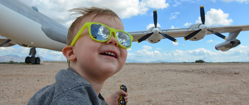 Excited child wearing sunglasses at an airport with a large airplane in the background