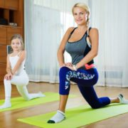 Happy young woman and little girl doing morning exercises indoors
